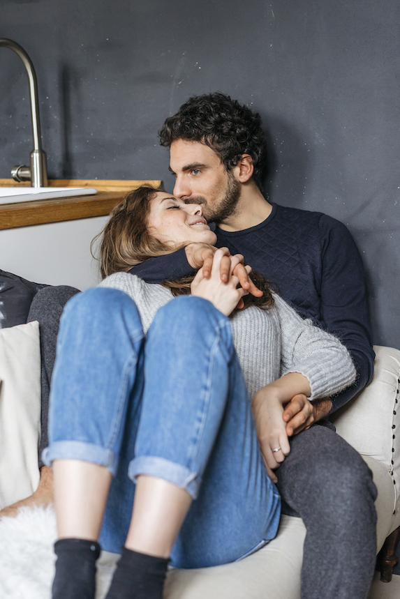 Couple holds hands while sitting on the sofa