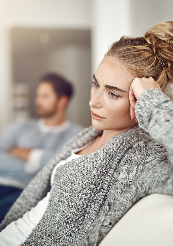 Woman sits on a couch with her boyfriend in the background, both looking frustrated