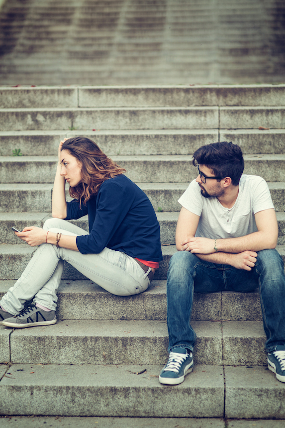 Man and woman sit on stairs outdoors looking frustrated with one another