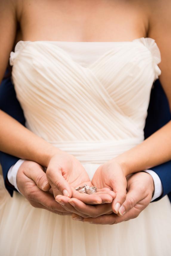A groom stands behind his bride