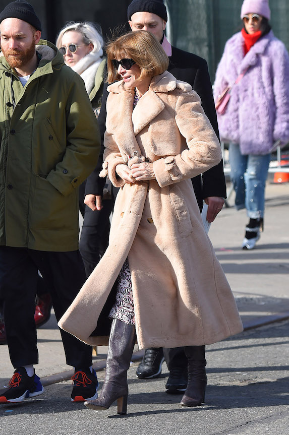 Vogue editor-in-chief Anna Wintour wears a textured winter coat and knee-high boots