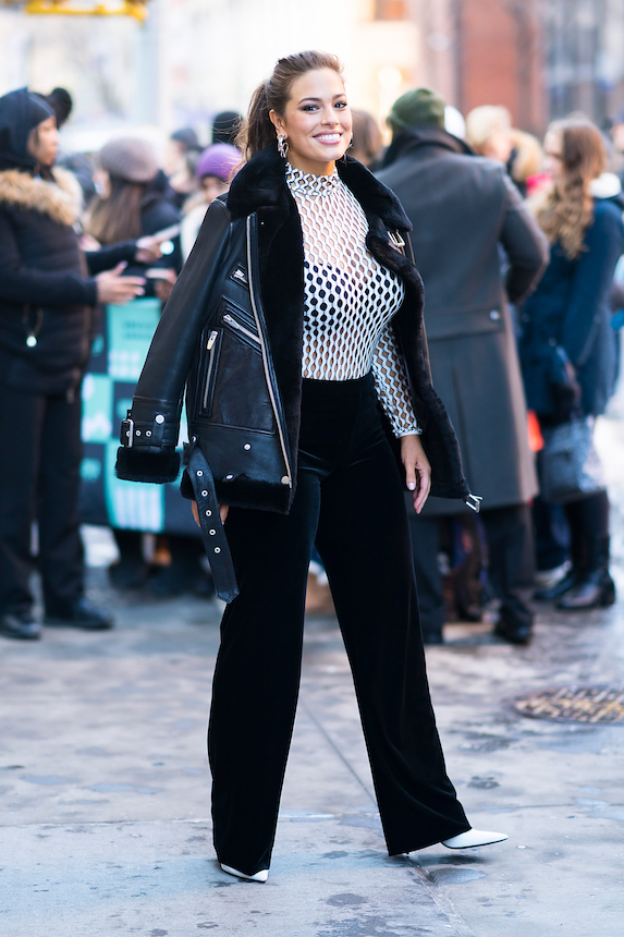 Model and activist Ashley Graham wears a black aviator jacket over a white netted top and black pants