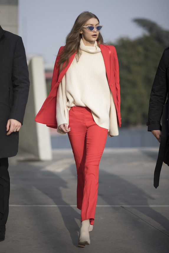 Gigi Hadid wears a red and beige outfit