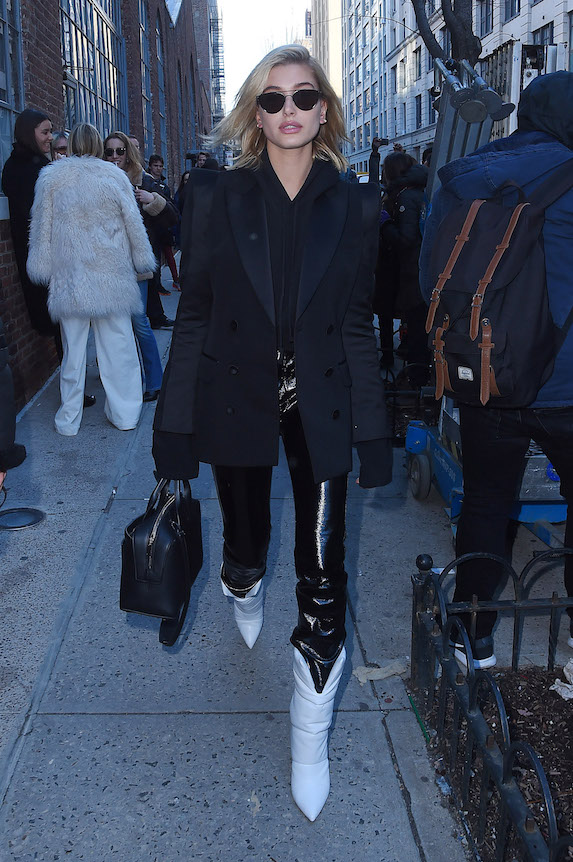 Hailey Baldwin wears a black coat, black patent leggings and white boots