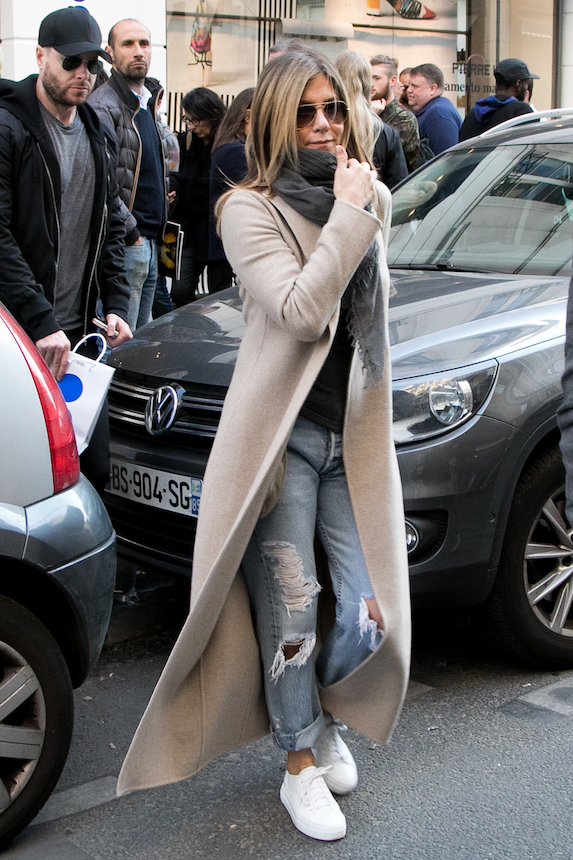 Jennifer Aniston wears jeans and white sneakers with a beige coat and scarf