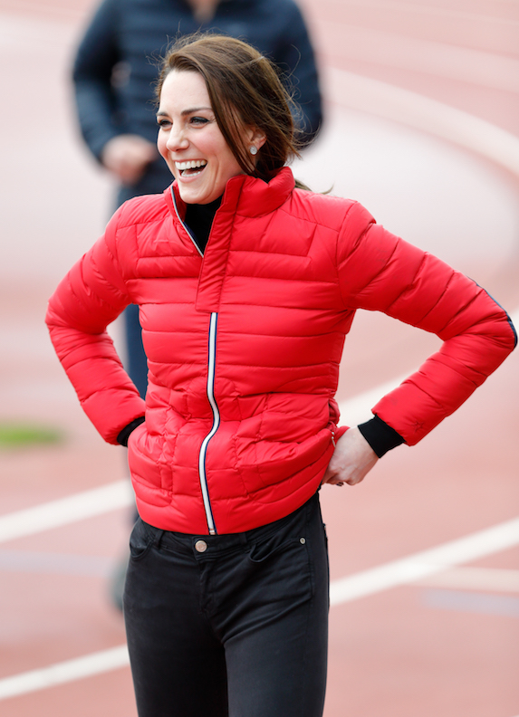 Kate Middleton wears black pants and top with a bright red puffer jacket