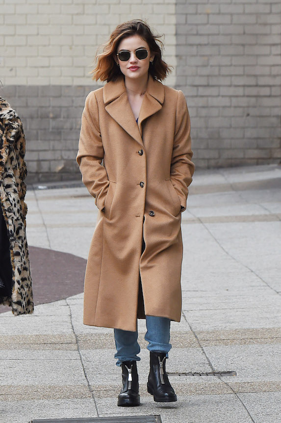 Actress Lucy Hale wears blue jeans, black flat boots and a camel overcoat