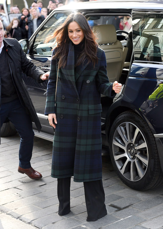 Meghan Markle wears black pants and top with a plaid overcoat