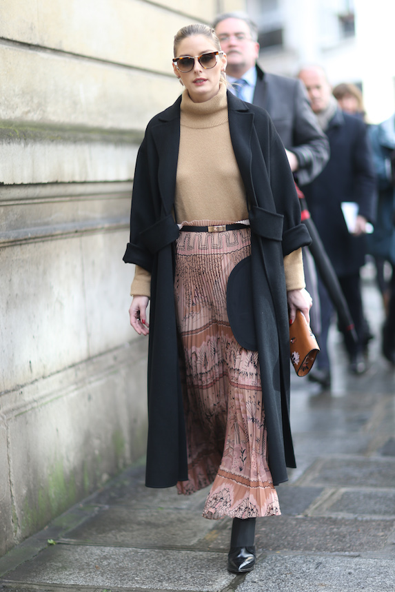 Olivia Palermo wears a skirt with knee-high boots