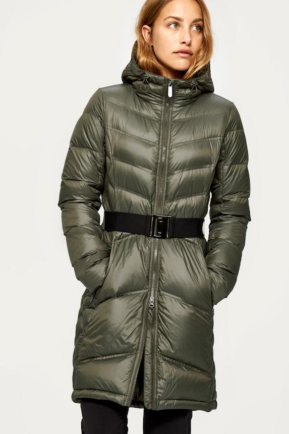 Model wears a long green belted winter coat