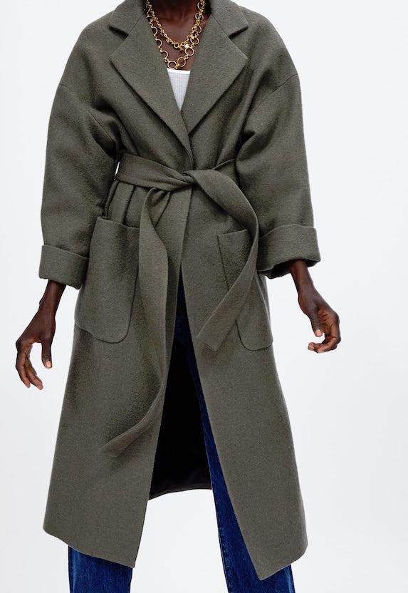 Model wears long green-tone belted coat in an oversized style
