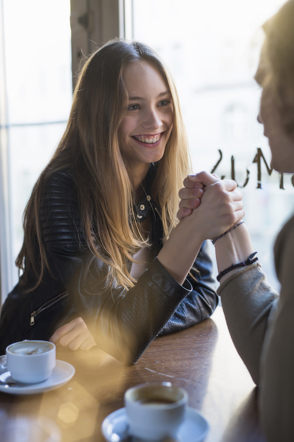 Smiling young woman and man hold hands over a table