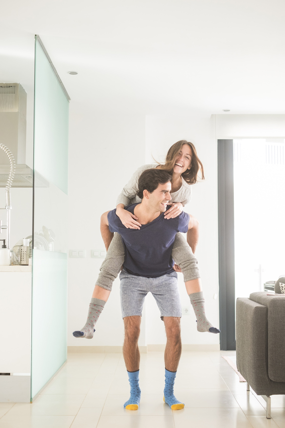 Man happily carries his girlfriend in piggyback through a home