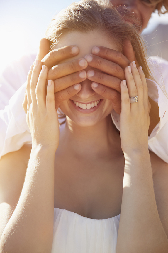 Woman smiles as man lovingly holds his hands over her eyes