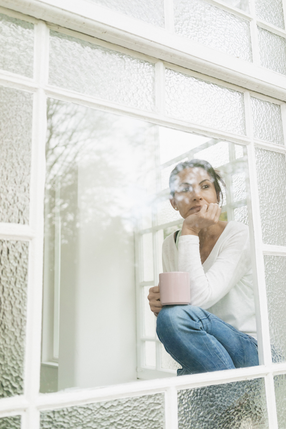 Woman sits reflectively by a window, holding a coffee mug