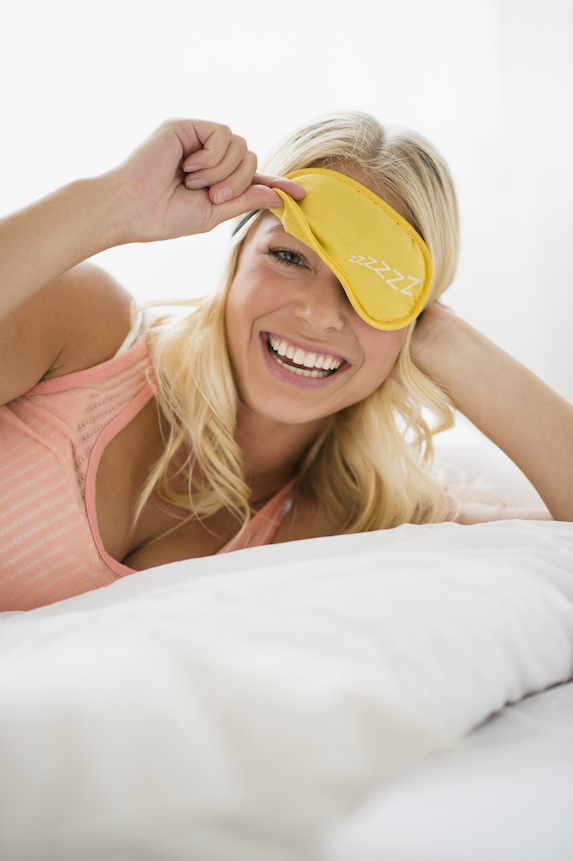 Blonde woman in bed playfully lifts her sleep mask