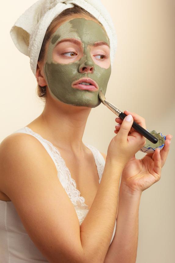 Woman applies green face mask