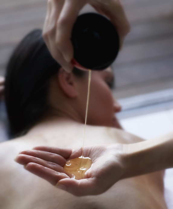 Masseuse pours liquid into hands for waiting spa client