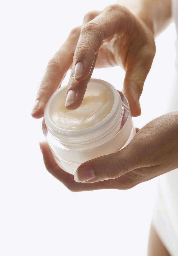 Woman's hands holding an open jar of cream