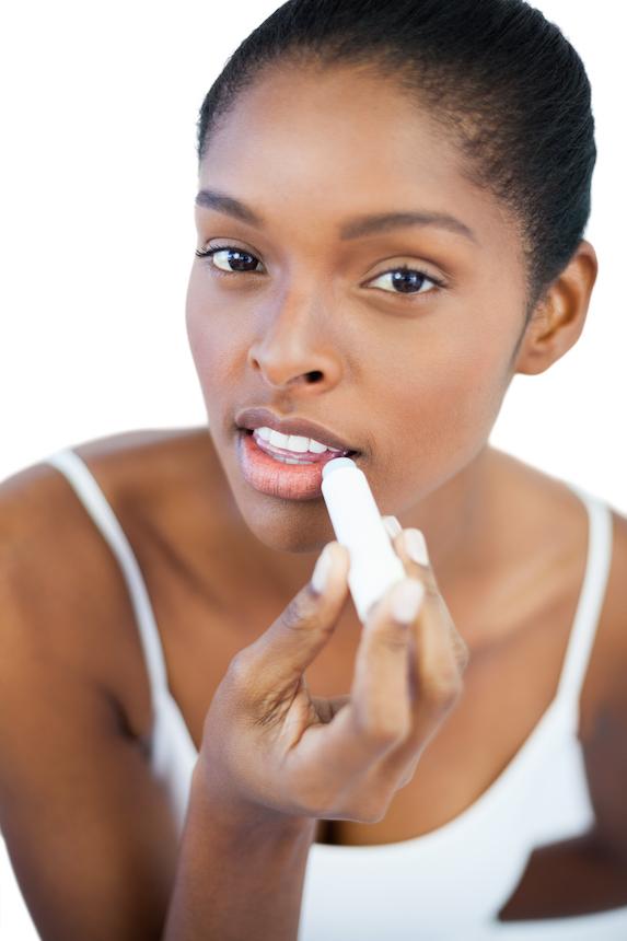 Woman applies lip balm