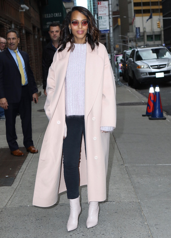 Kerry Washington wears white booties, a light-coloured sweater and white overcoat