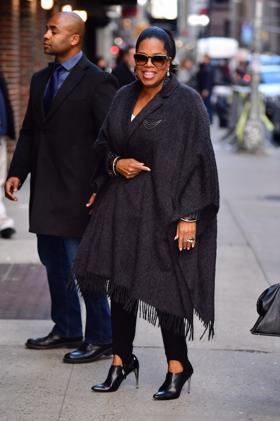 Oprah wears a fringed overcoat and black leggings with ankle boots