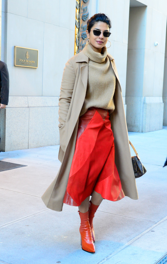 Priyanka Chopra wears a beige turtleneck and coat with a red skirt and booties