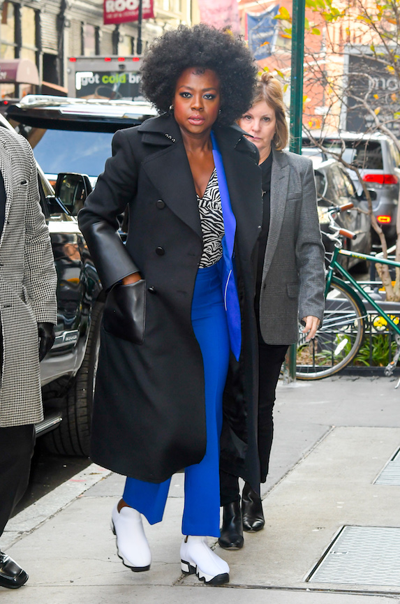 Actress Viola Davis wears a black coat, blue suit and white sneakers