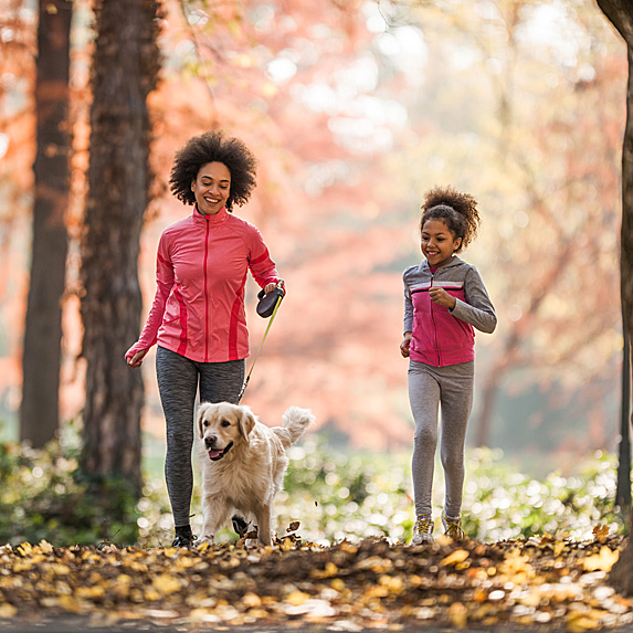 Mother and daughter walking in the woods with golden retriever