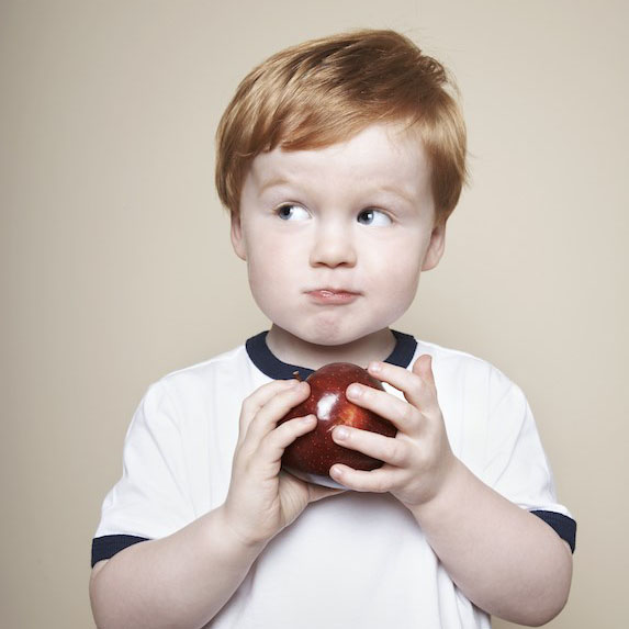a young boy eating an apple