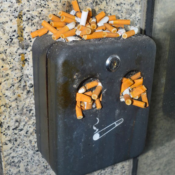 cigarette stubs in an outdoor ashtray