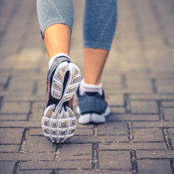 a woman's legs in exercise cloths and running shoes