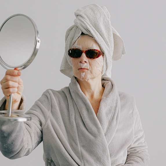 Older woman wearing face mask and sunglasses looking at herself in the mirror