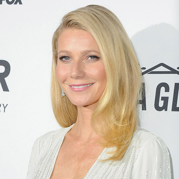 Actress Gwyneth Paltrow arrives at amfAR's Inspiration Gala Los Angeles wearing a deep v-neck white blouse.