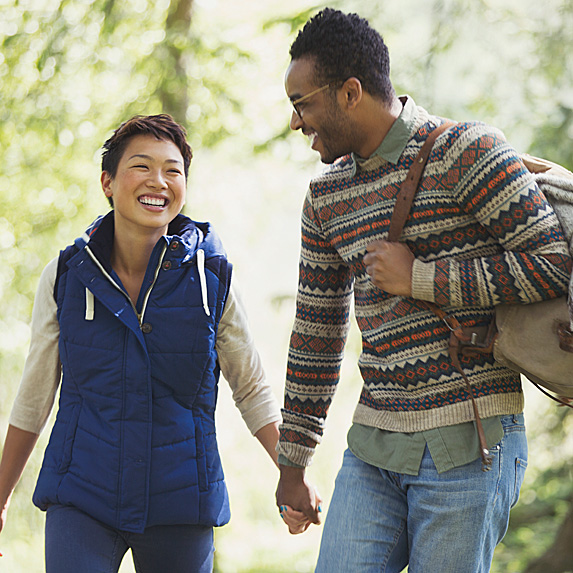 Woman and man walking in woods, holding hands, smiling
