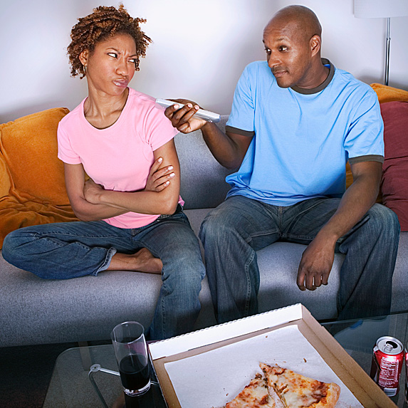 Woman and man lightly fighting over remote and pizza