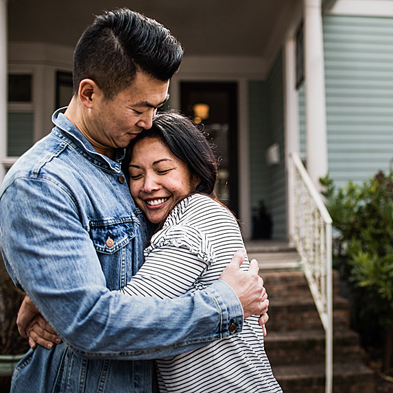 Man and woman embracing outside house
