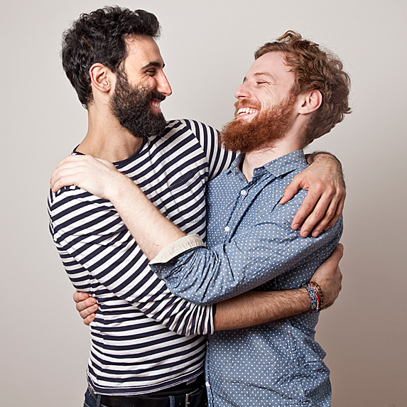 Two men grinning with arms around each other