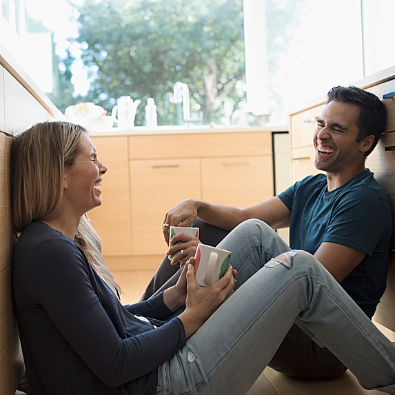 Woman and man laughing, holding mugs, sitting on kitchen floor