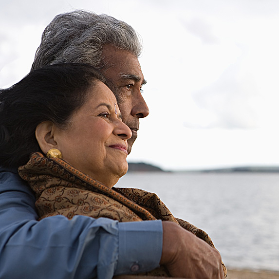 Man with arm around woman as they stare at water