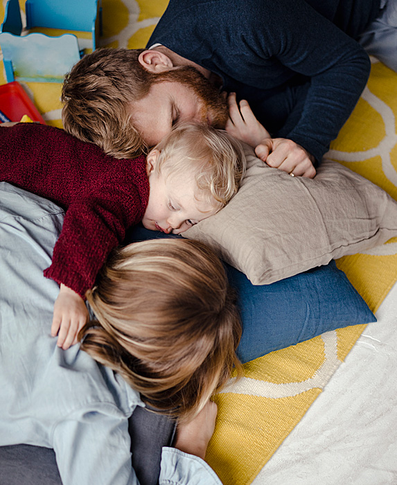 Woman and man napping with toddler