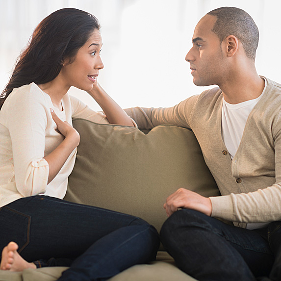 Woman and man on sofa having a serious discussion