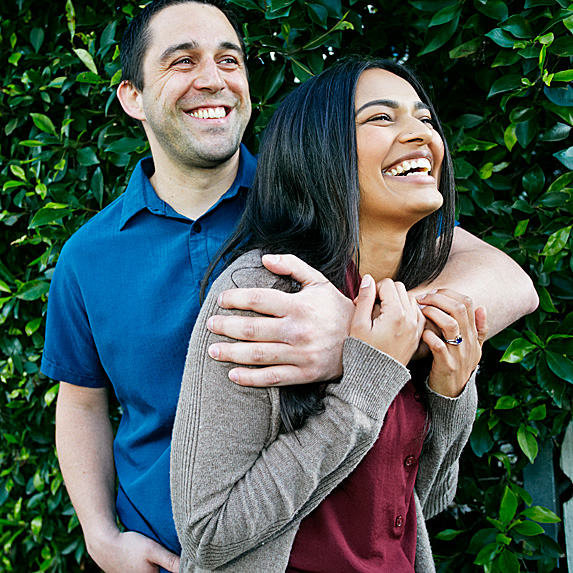 Man with arm around woman, both are laughing
