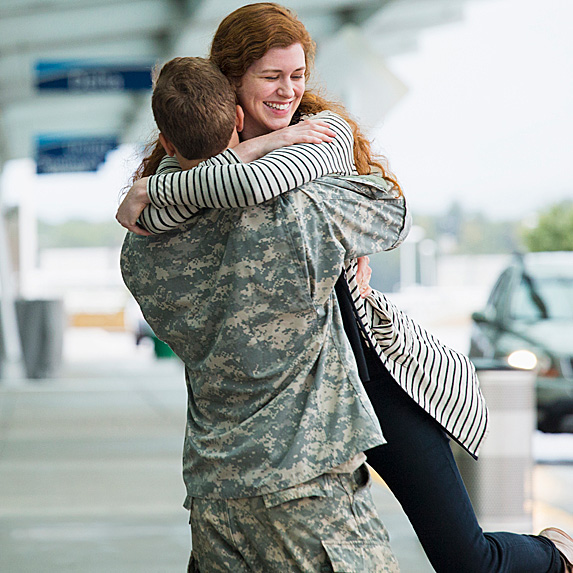 Soldier picking up wife and twirling her at airport