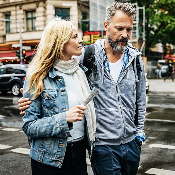 Woman and man, talking and walking along street