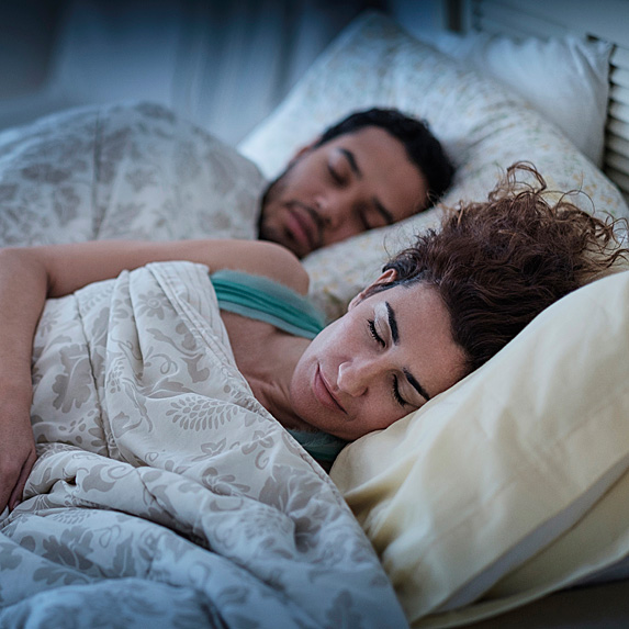 Man and woman asleep in bed