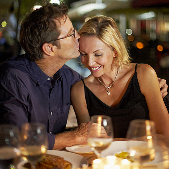 Man kissing woman's head during dinner date