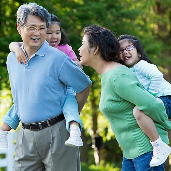 Mature man and woman piggybacking children