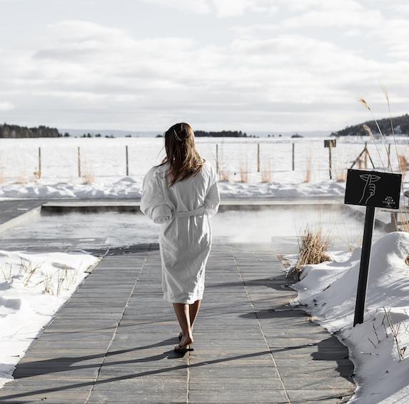 Woman in a robe walks towards an outdoor spa facility at Spa Nordique