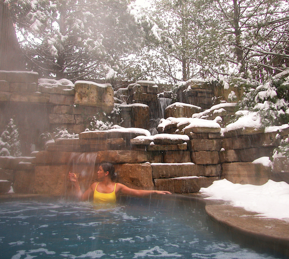 A woman enjoys the outdoor hot springs pool at 100 Fountain Spa